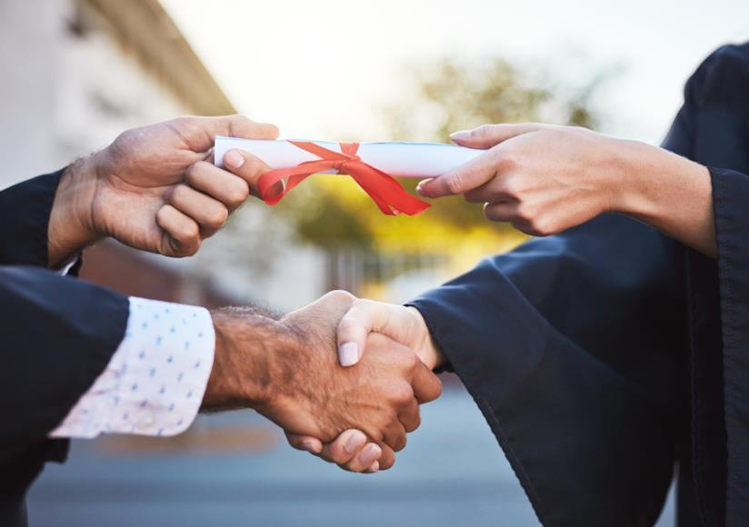 Un professore stringe la mano di un laureato