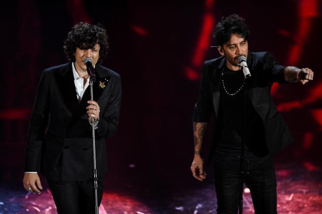 Ermal Meta e Fabrizio Moro, in piedi, di fronte a un microfono, vestiti di nero, con sfondo rosso