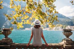 Una ragazza seduta su un parapetto osserva il mare