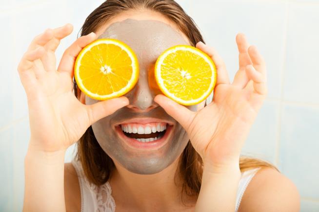 Una donna sorride con applicata sul viso una maschera purificante