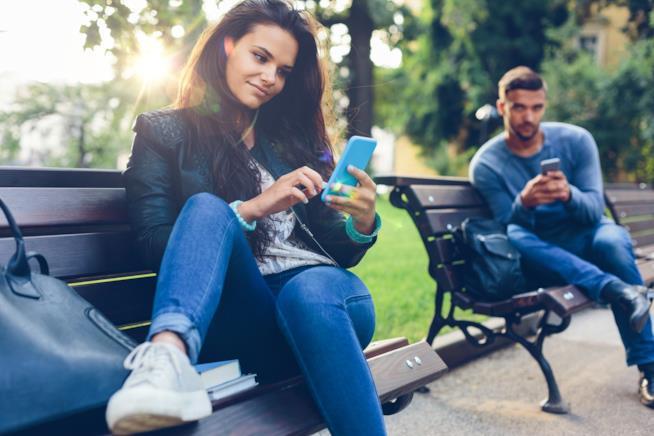 Un ragazzo e una ragazza chattano con lo smartphone al parco