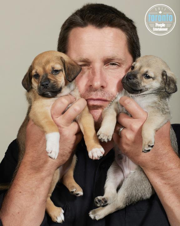 Christian Bale tiene in braccio dei cuccioli