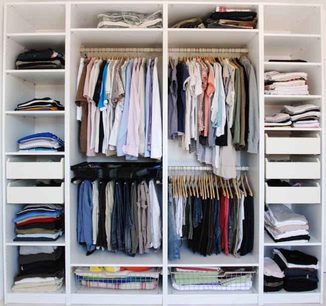 Visione di un armadio ordinato con vestiti ben piegati e divisi per genere