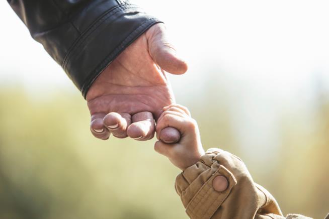 La mano di un bambino stringe il dito di un uomo