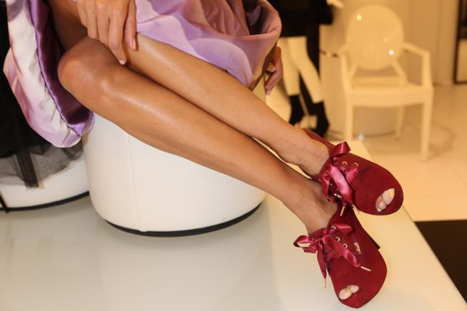 Una donna dalle gambe perfettamente lisce indossa un paio di scorpe rosse