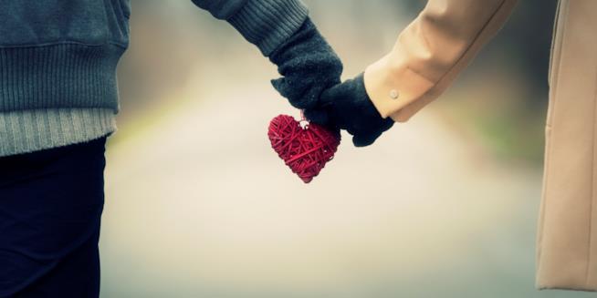 Due persone si tengono per mano con un cuore fatto di spago rosso