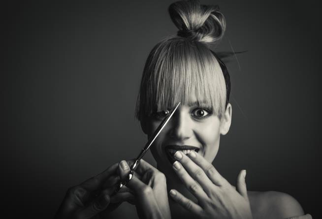Ragazza con forbice che taglia i capelli