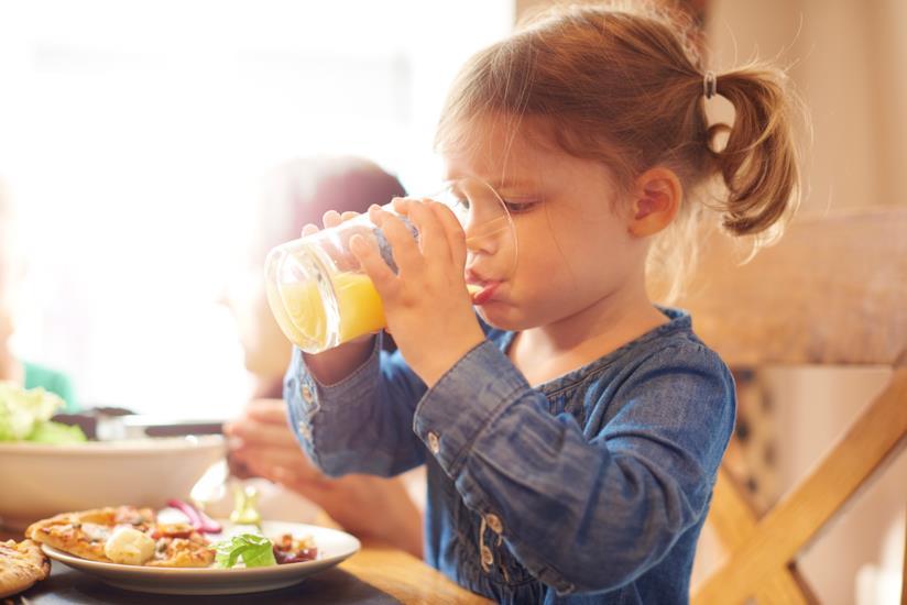Bambina che beve il succo