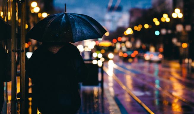 Uomo cammina in città sotto l'ombrello