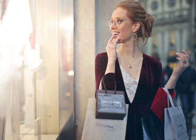 Donna davanti una vetrina con le buste
