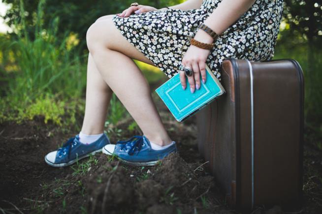 Ragazza con libro e valigia