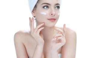 Primo piano di una ragazza con addosso un asciugamano e uno sui capelli e della crema sulle guance