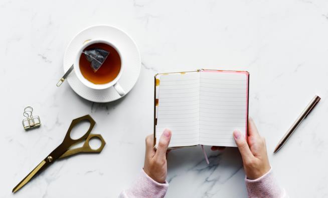 Un diario, forbici e una tazza di tè