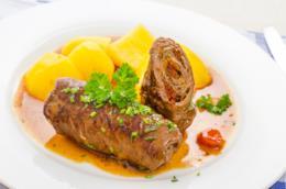 Piatto bianco con all'interno due braciole di carne di cui una intera e l'altra a metà con patate.