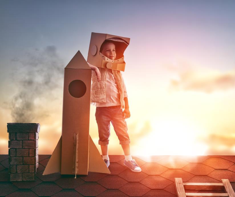 Bambino sul tetto di una casa vestito da astronauta
