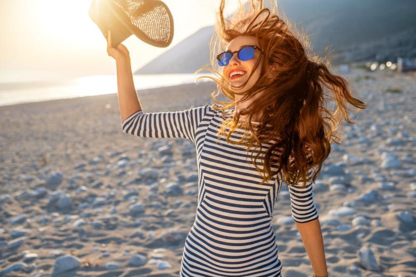 Ragazza con capelli ricci in spiaggia