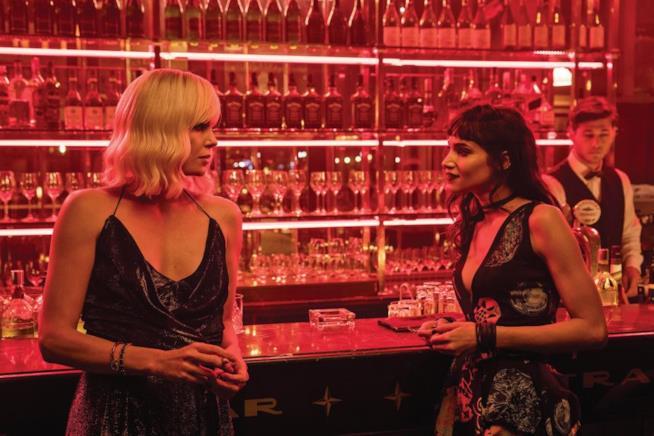 Charlize Theron e Sofia Boutella bevono un drink in una scena di Atomica Bionda