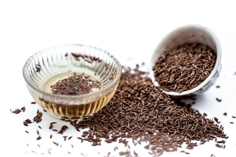 Ciotola con semi di cumino e acqua di cumino