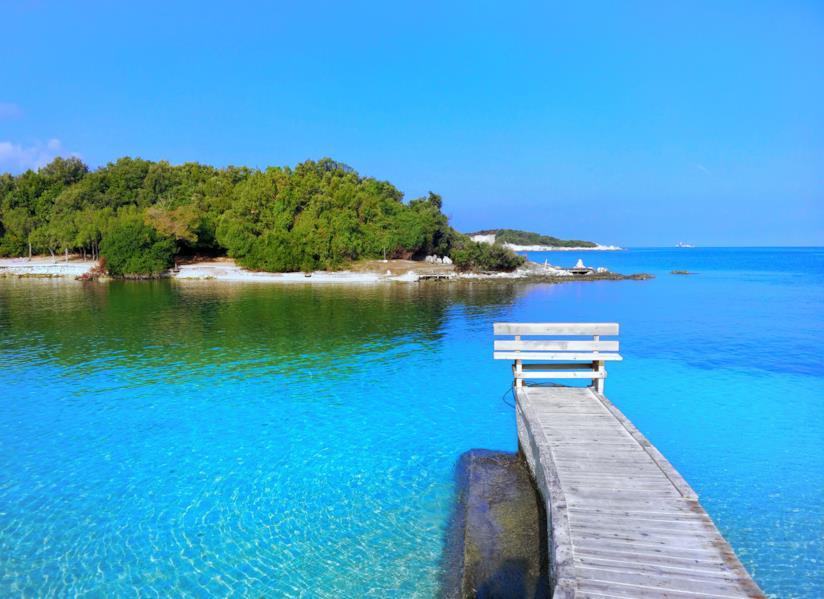 Il mare turchese lambisce le coste delle isole di Ksamil ricche di vegetazione.