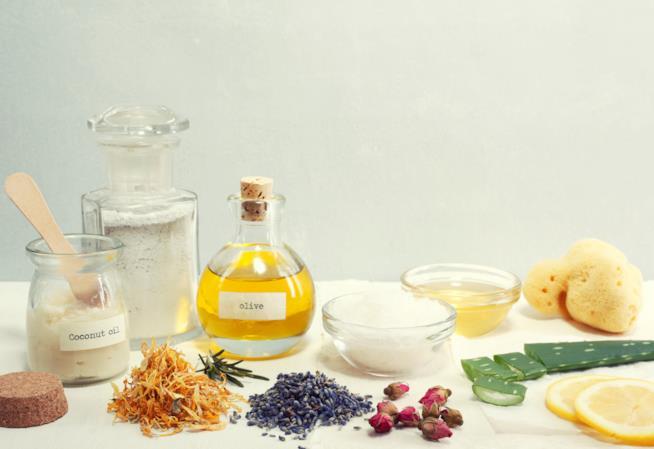 Cinque flaconi contenenti olio e polveri, una spugna circondati da verdure e erbe naturali