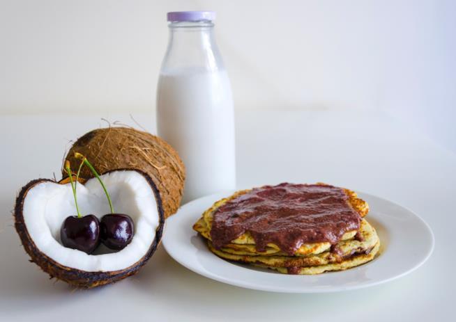 Pancakes in un piatto con il cocco vicino