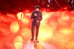 Francesco Renga, in piedi, canta di fronte al microfono, su sfondo arancione