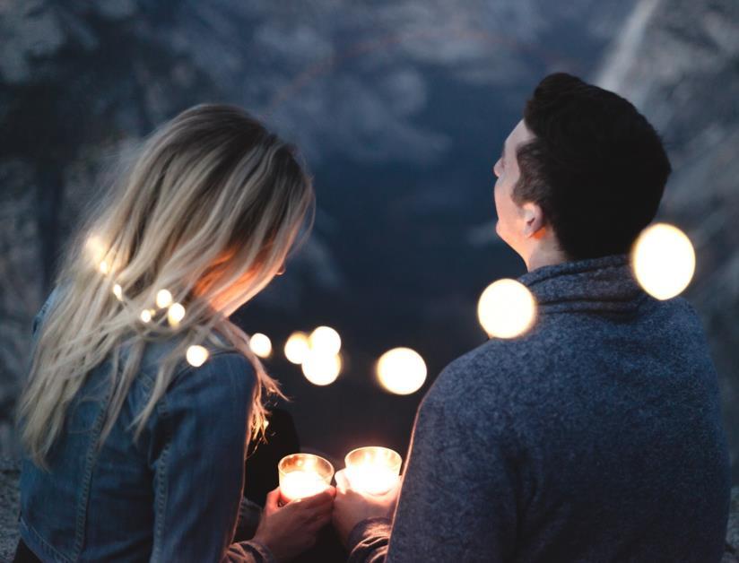Un ragazzo e una ragazza di spalle con due bicchieri in mano