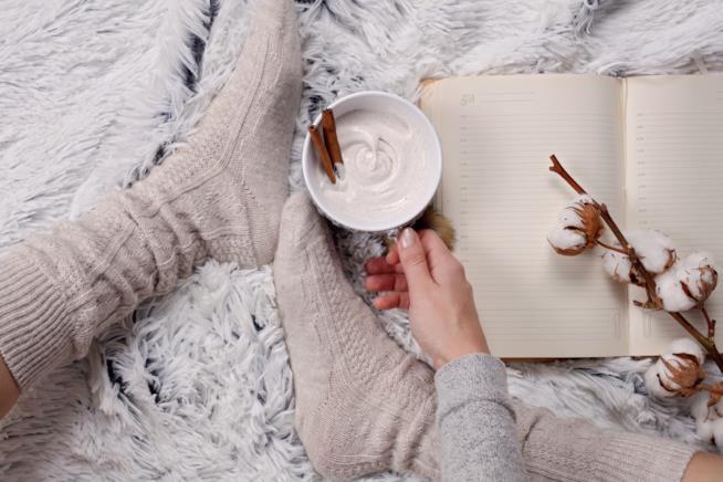 Una ragazza su un letto con i piedi al caldo