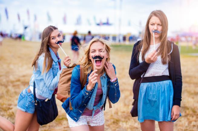Ragazze scherzano indossando baffi finti
