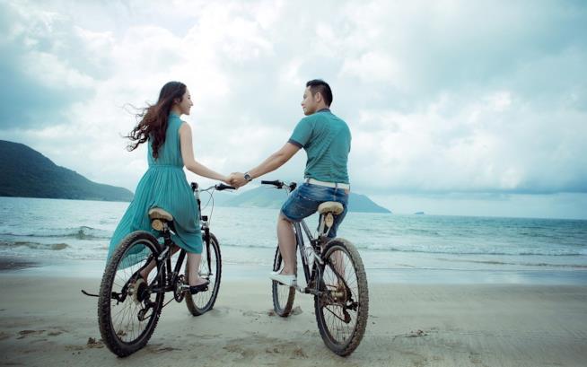 Fidanzati in bicicletta in spiaggia