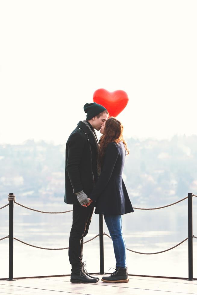 Una giovane coppia si bacia su un pontile