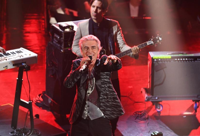 Ligabue, in piedi, in nero, canta al microfono e sorride, davanti al bassista