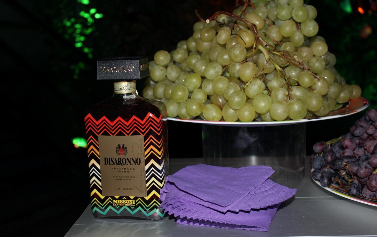 La bottiglia di Disaronno wears Missoni al fianco di un vassoio d'uva.