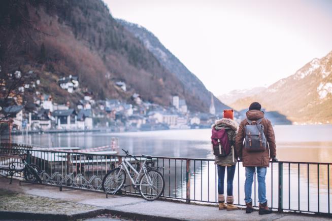 Due ragazzi con vestiti invernali guardano il panorama di un lago con le montagne intorno