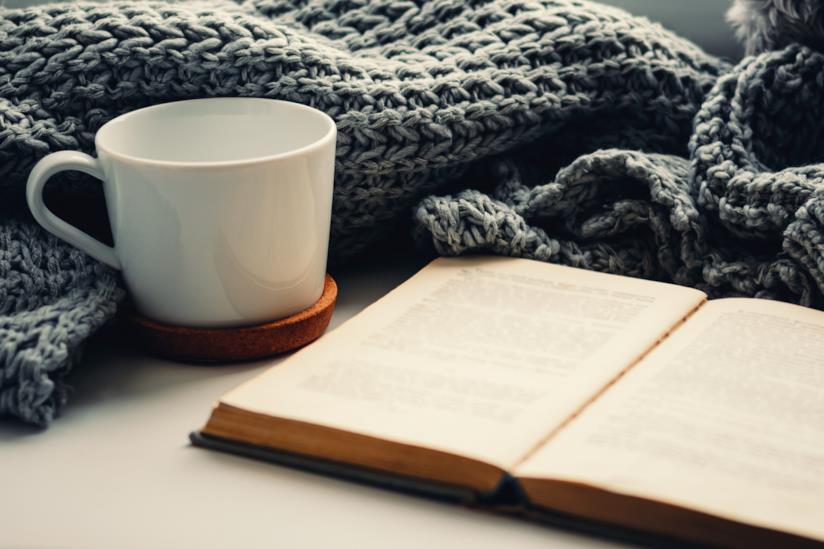 Libro aperto vicino una tazza