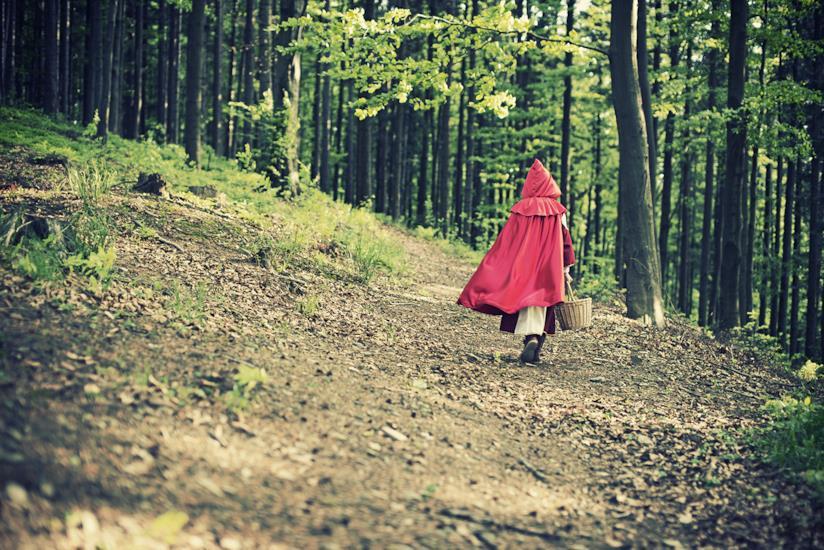 Bambina vestita come Cappuccetto rosso in un bosco