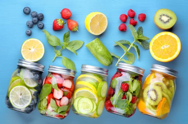 Cinque barattoli con frutta colorata all'interno ed intorno ad essi