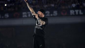 J-Ax, a San Siro, vestito di nero, canta al microfono in piedi