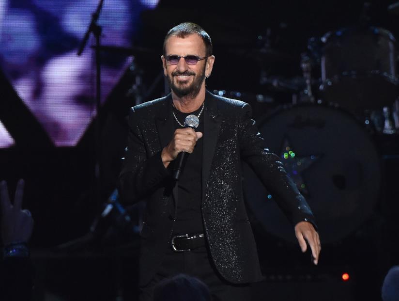 Ringo Starr in nero, in piedi, col microfono in mano, davanti a una batteria