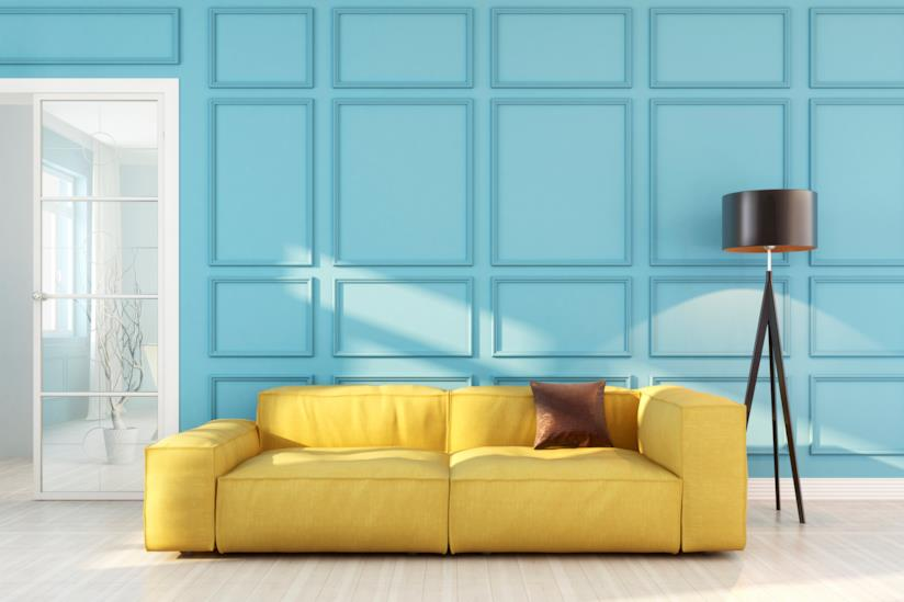 ampio divano in soggiorno illuminato da una lampada da terra posta di lato