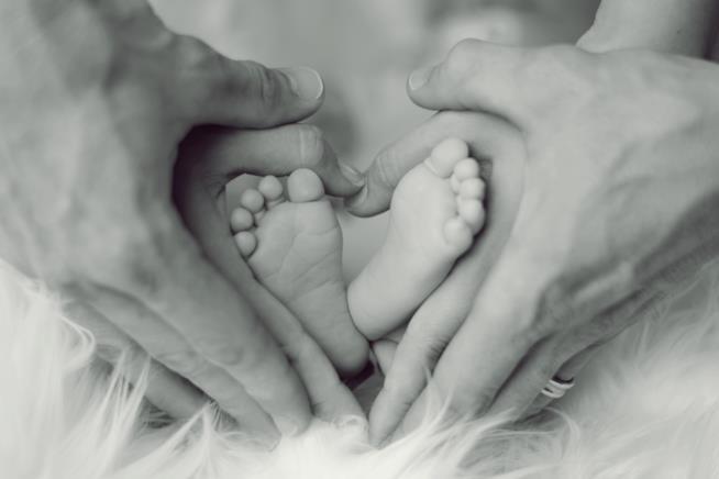 Mani di uomo e donna intorno ai piedi di un neonato