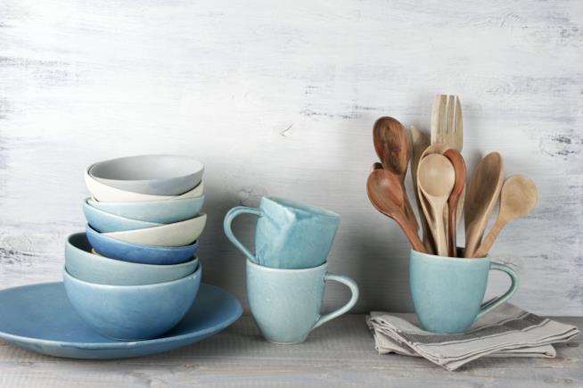 Stoviglie in ceramica in colori pastello e legno impilate sulla mensola della cucina