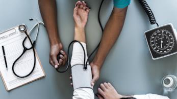 Un medico che misura la pressione ad una donna.