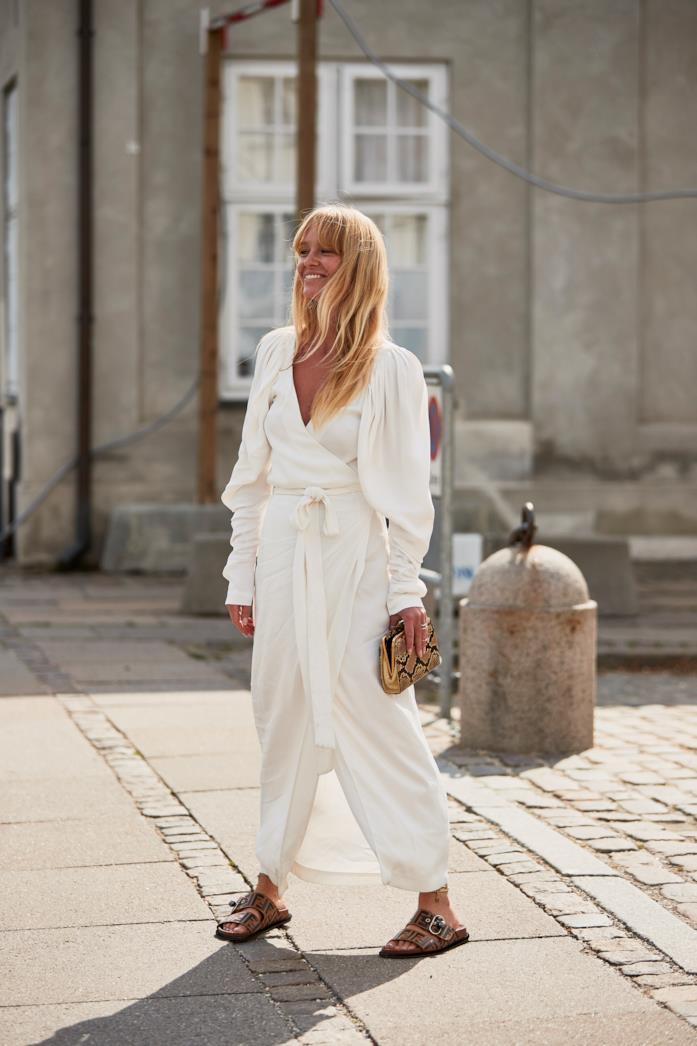 Jumpsuit bianca abbinata a ciabatte Birkenstock e pochette animalier