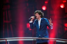 Ermal Meta, in piedi, canta al microfono, con una giacca blu, su uno sfondo rosso.