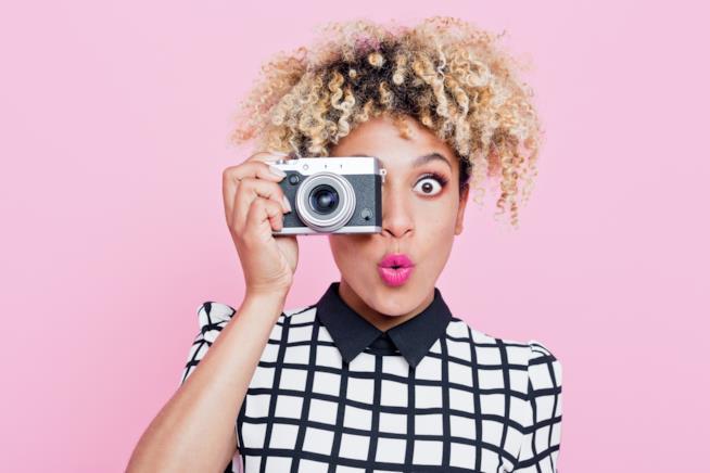 Una modella con capelli ricci e macchina fotografica