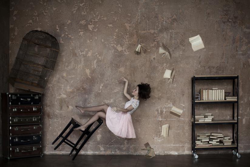 Donna in una stanza con libri volanti intorno