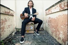 Eddie Vedder con una chitarra in mano, seduto su una valigia, vestito di nero