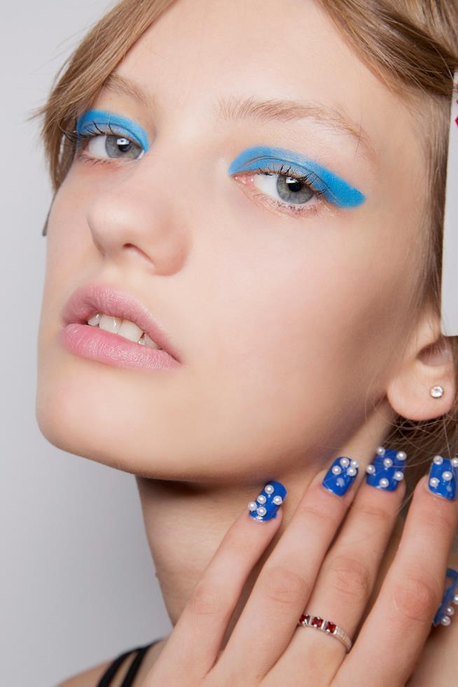 Nail art gel blu con decorazioni bianche
