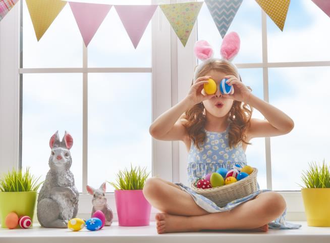 Bambina gioca con uova dipinte